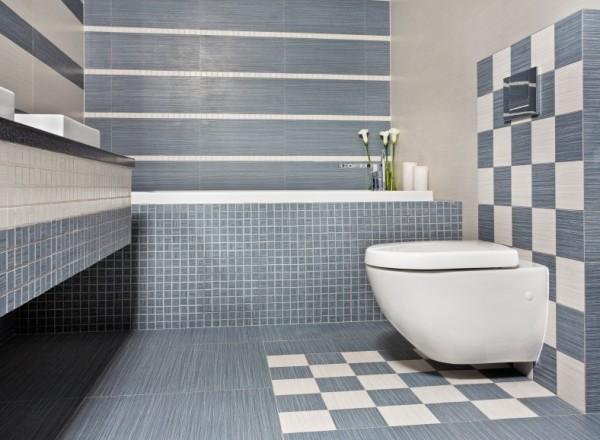 Der einheitliche Grauton fügt verschiedene Formate zu einer Einheit zusammen – und trennt das Bad gleichzeitig in verschiedene Nutzungsbereiche.