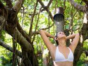 Frau unter exotischer Dusche im Freien