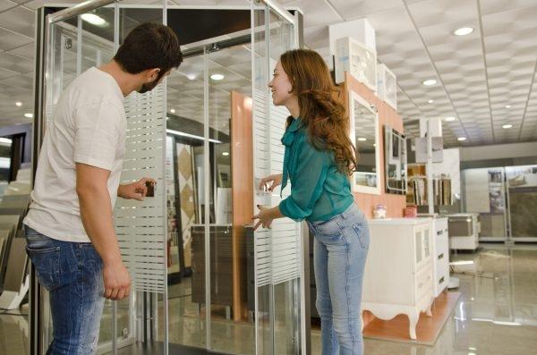Mann und Frau schauen sich in einer Ausstellung eine Dusche an