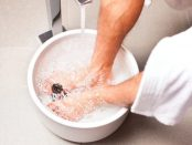 Mann nimmt ein Fußbad zuhause in einem Eimer