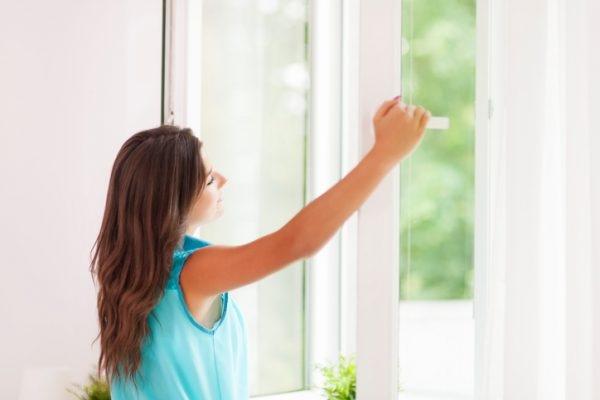 Frau öffnet das Fenster zum Lüften