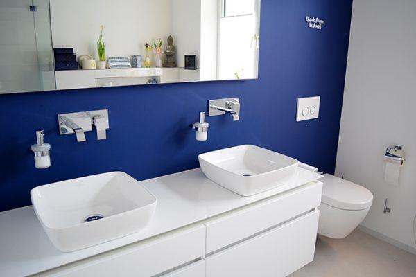 Badezimmer mit weißem Waschtisch und blauer Wandfarbe