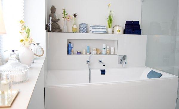 weiße, moderne Badewanne mit Deko und Badutensilien