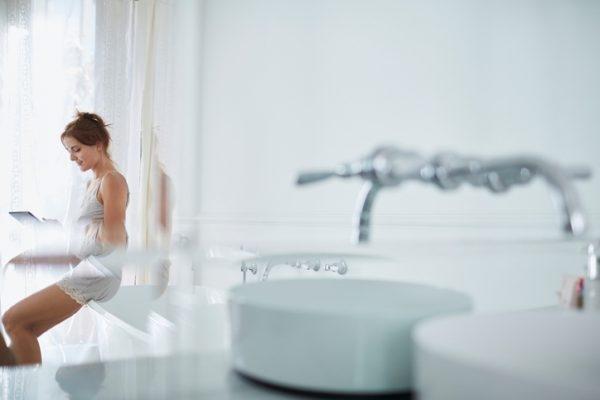 Frau sitzt mit Tablet im Bad