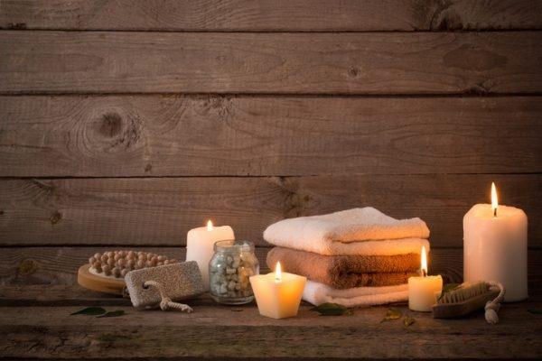 Kerzen und Handtücher auf Holzablage