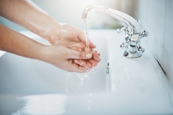 Hände unter laufendem Wasserhahn