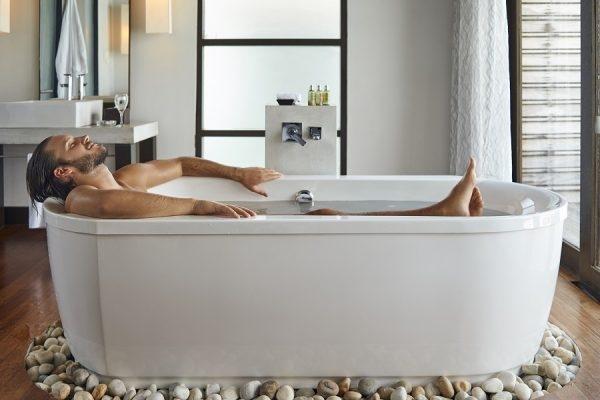 Mann liegt in Badewanne
