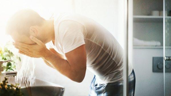 Mann benetzt sein Gesicht mit Wasser