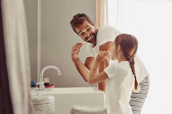 Vater und Tochter im Bad beim Zähneputzen.